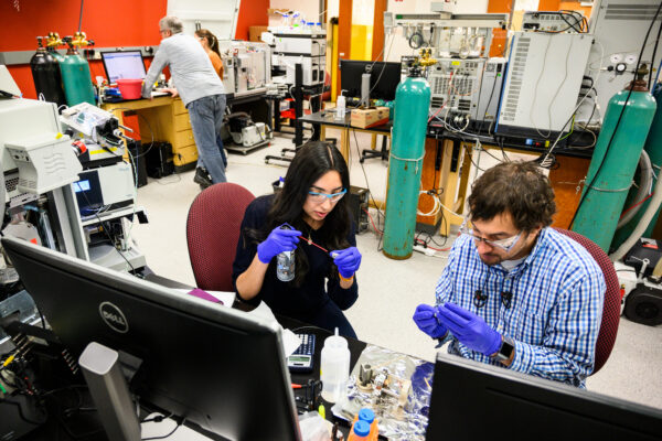 Two people wearing gloves and handling research equipment