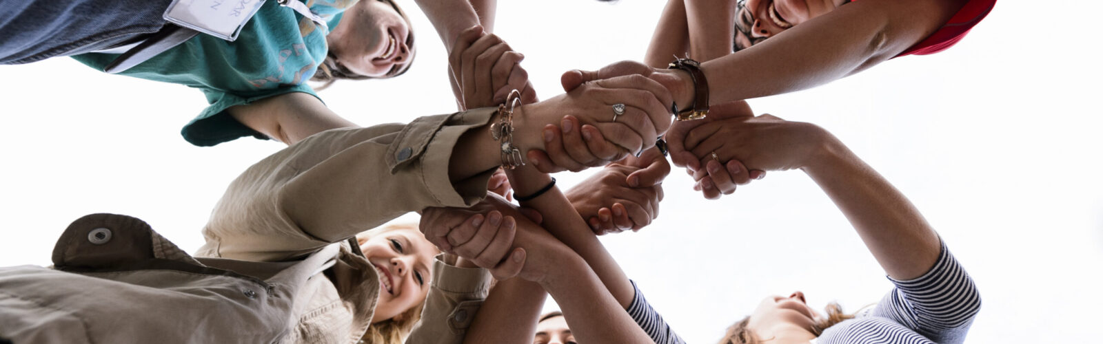 Close-up of huddled people with interlocking hands